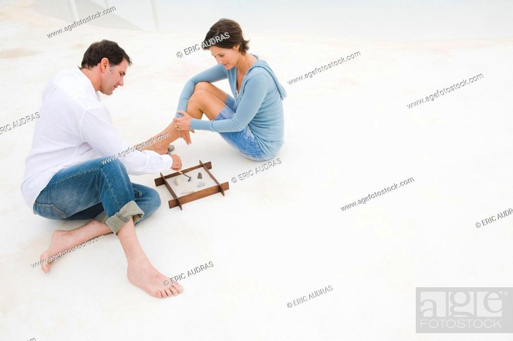 Stock Photo: Couple playing with a sandbox.