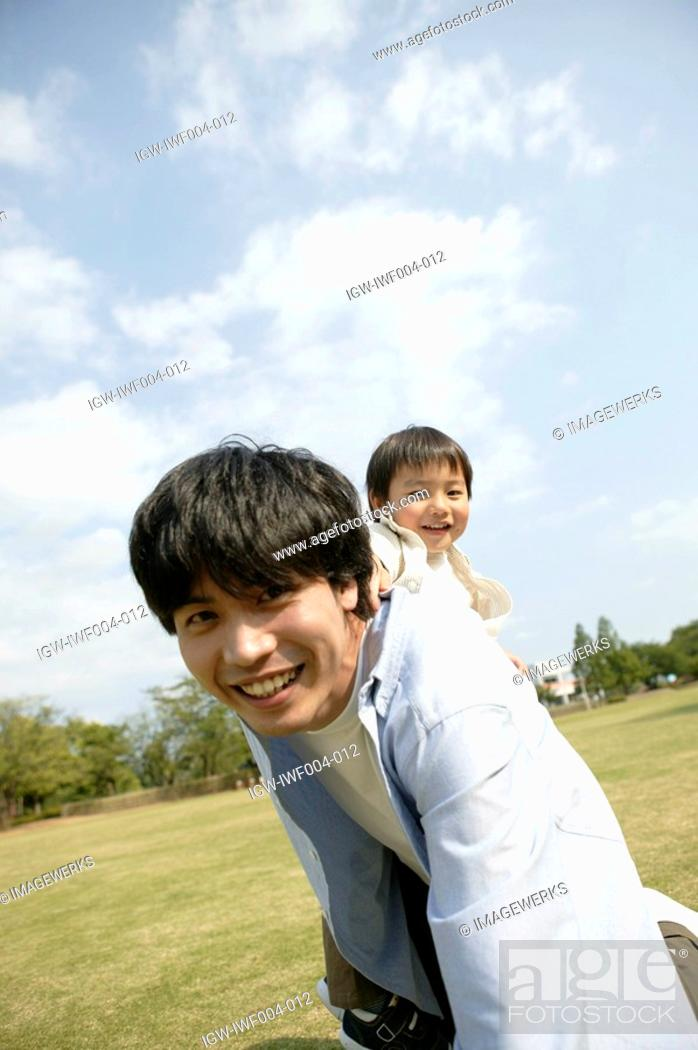 Stock Photo: Son enjoying himself as he sits on his fathers back.