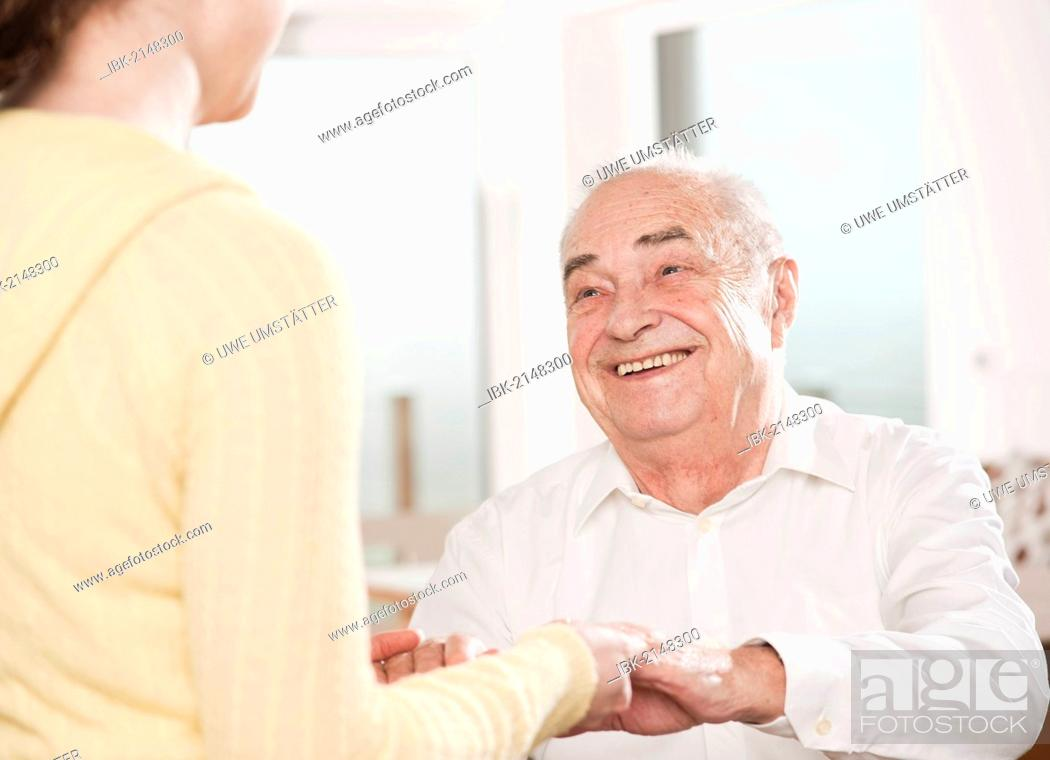 Stock Photo: Young woman taking care of an elderly man.