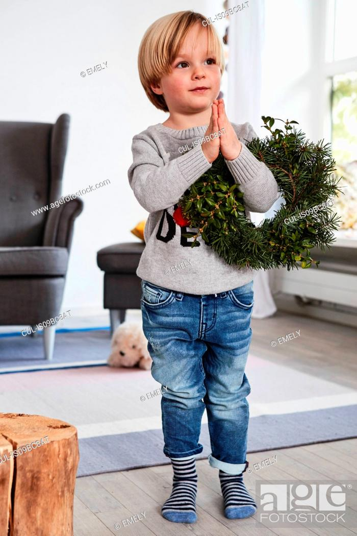 Stock Photo: Young boy standing with hands together, holding wreath over arm.