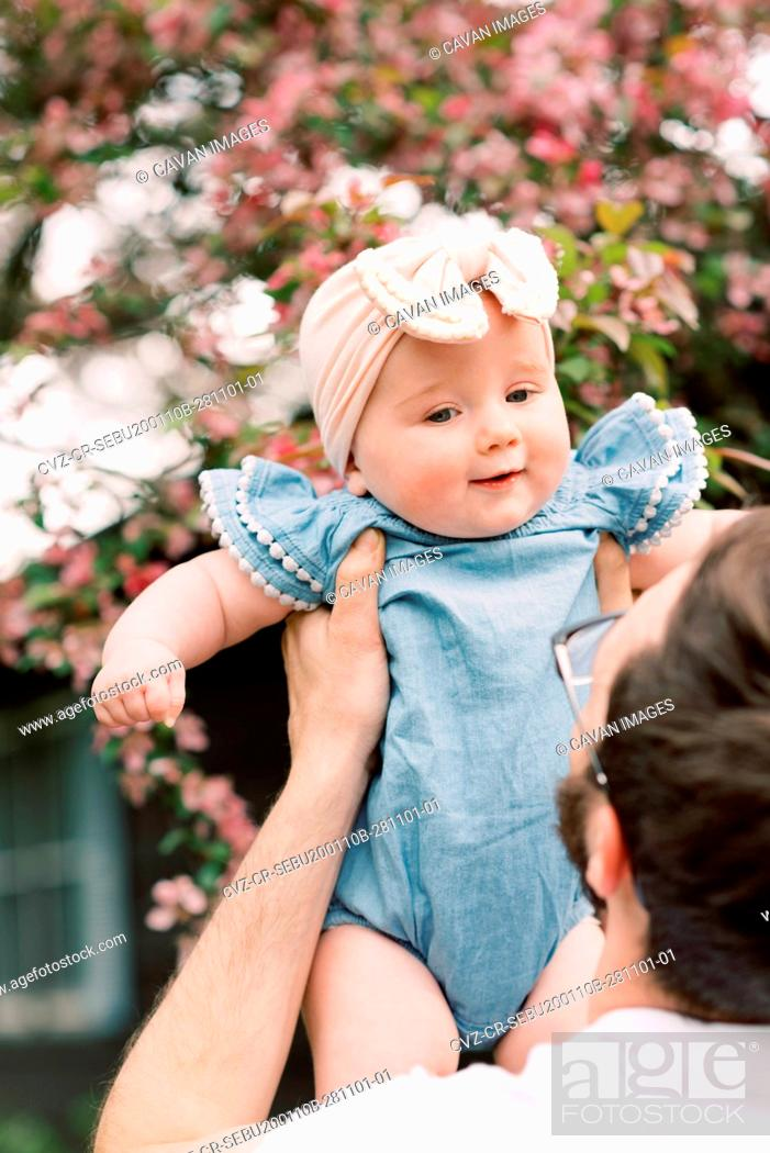 Stock Photo: Little baby girl being held by her father.