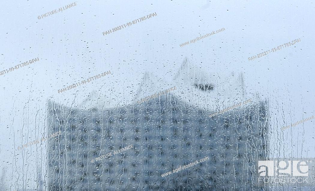 Stock Photo: 11 February 2020, Hamburg: Raindrops fall on a window pane through which the Elbphilharmonie can be seen. Photo: Axel Heimken/dpa.