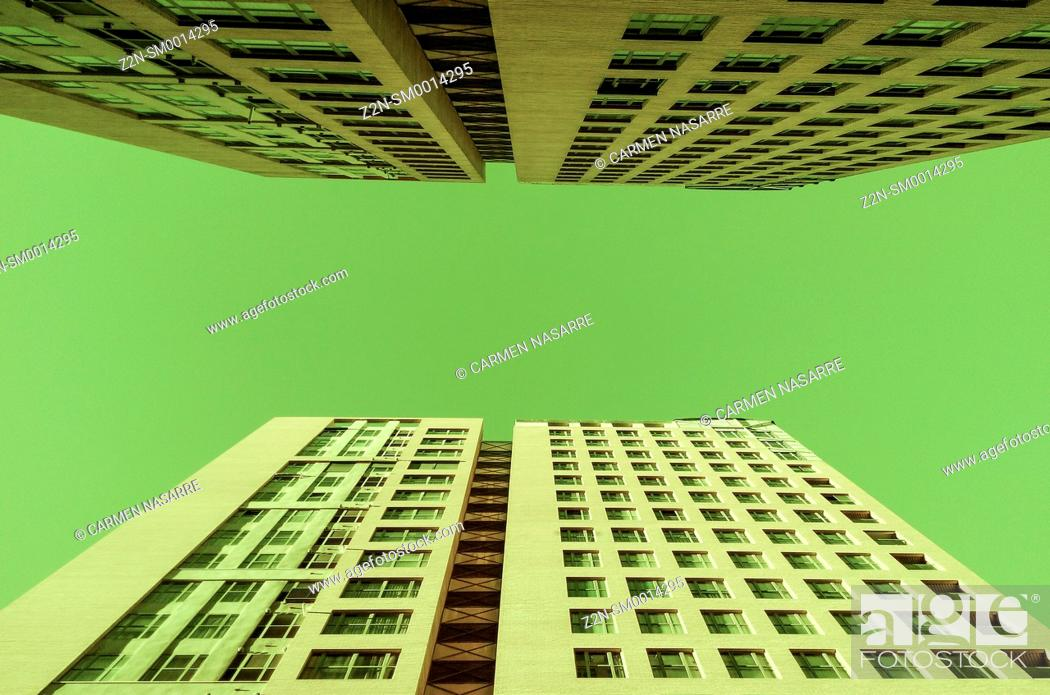 Stock Photo: Two buildings under green sky.