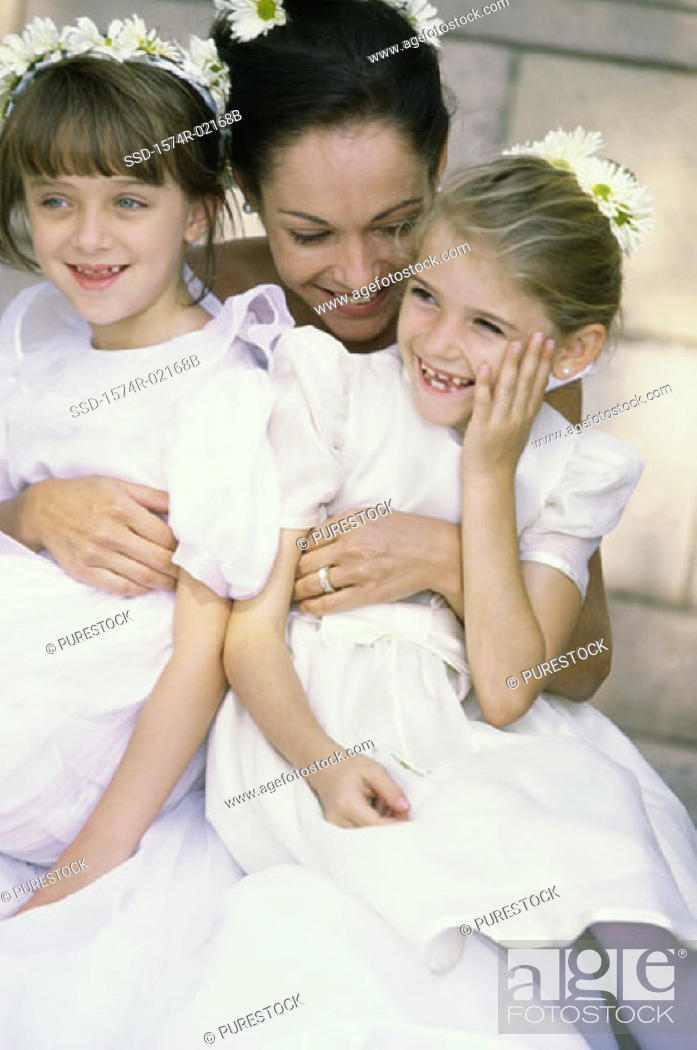 Stock Photo: Bride hugging two flower girls.
