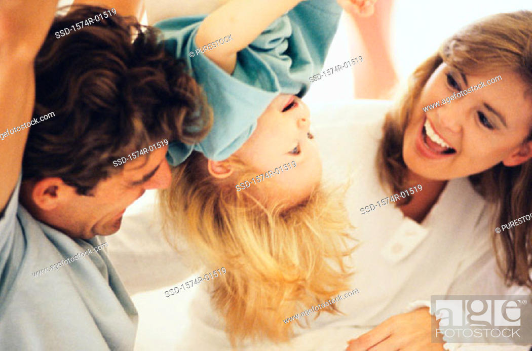 Stock Photo: Father and mother playing with their daughter.