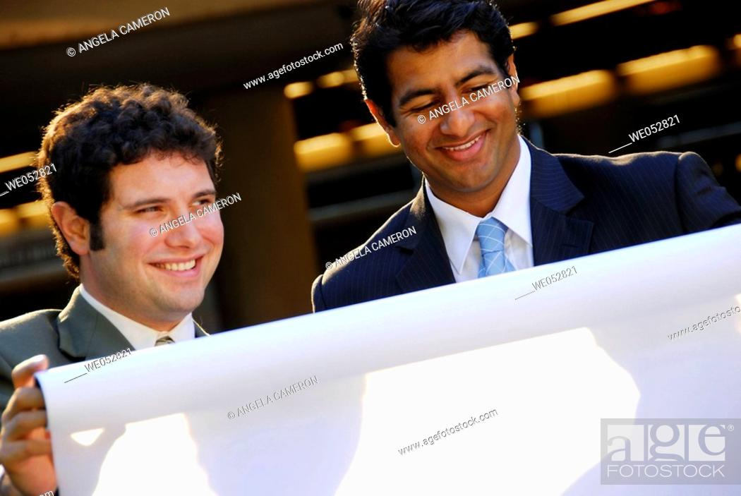 Stock Photo: 2 young male business men holding architect plans.