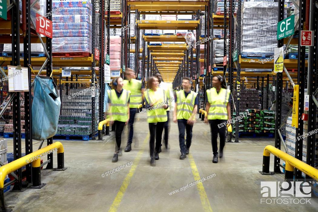 Photo de stock: Staff in reflective vests walking to camera in a warehouse.