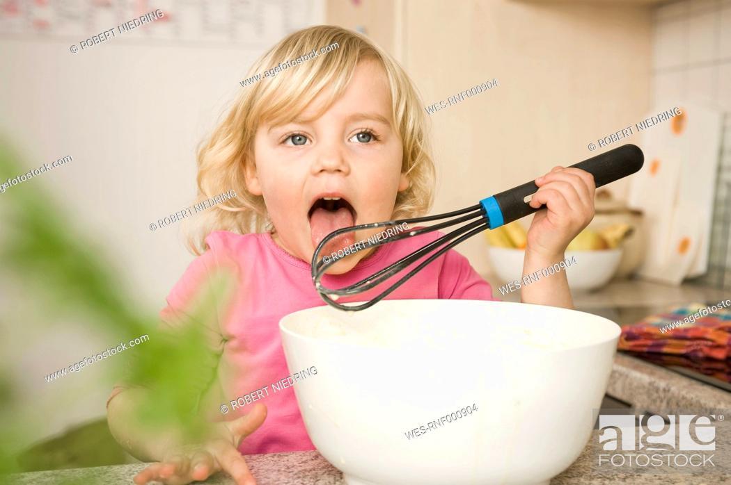 Stock Photo: Girl preparing cake, tasting batter.