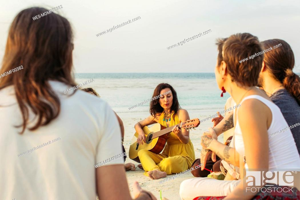 Imagen: Thailand, Koh Phangan, group of people sitting on a beach with guitar.