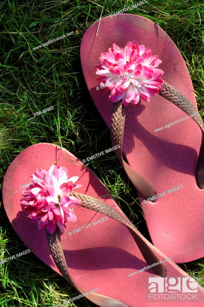 Stock Photo: Pink flip flops with a blossom.