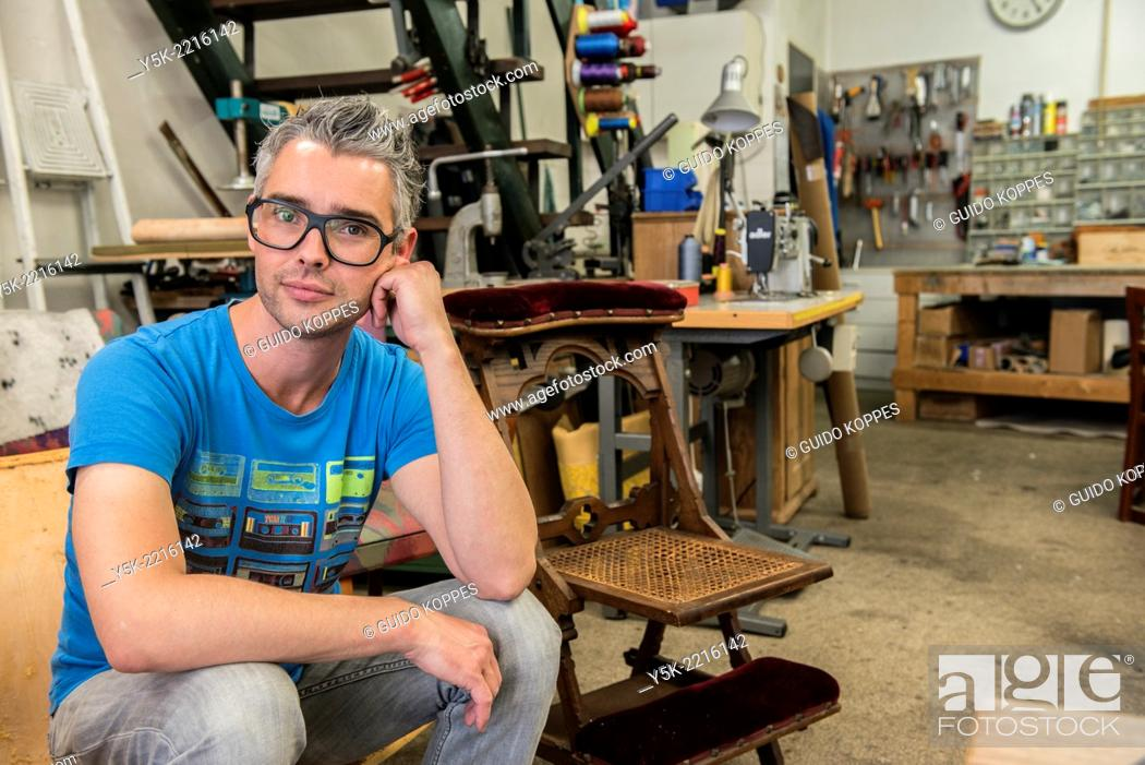 Stock Photo: Tilburg, Netherlands. Josef is an apprentice upholsterer, soon taking over the workshop from the 72 year old upholsterer 'Boy'.