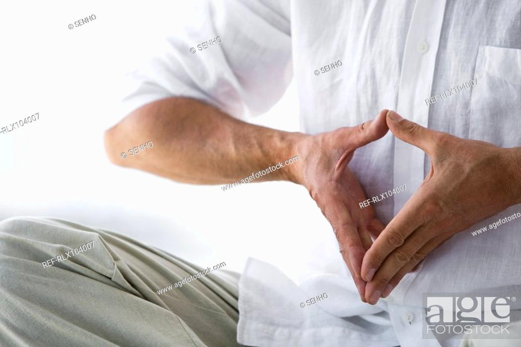 Stock Photo: Senior man sitting, doing Yoga exercise, detail of hands indoors.