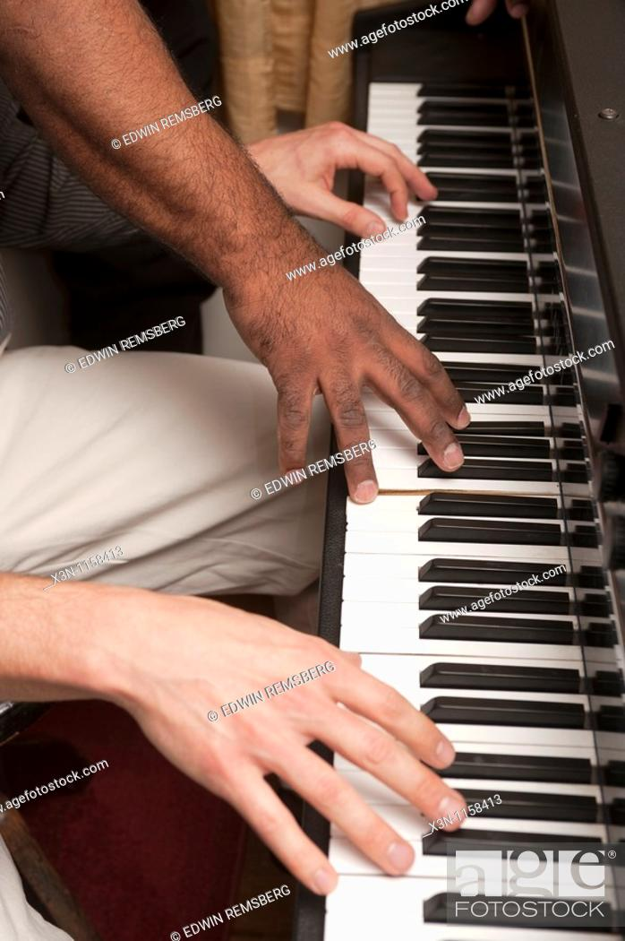 Stock Photo: Hands on a piano keyboard.