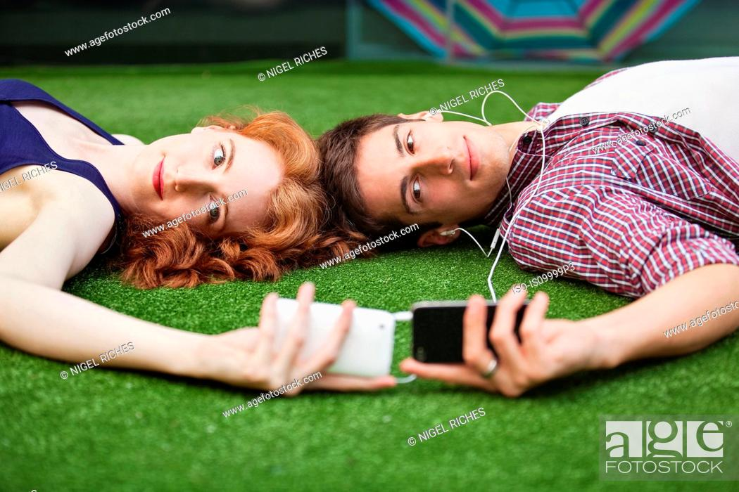 Stock Photo: Couple lying down looking at mobile phones.