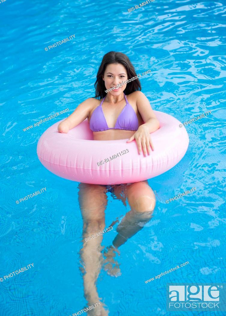 Imagen: Mixed race amputee woman swimming in pool.