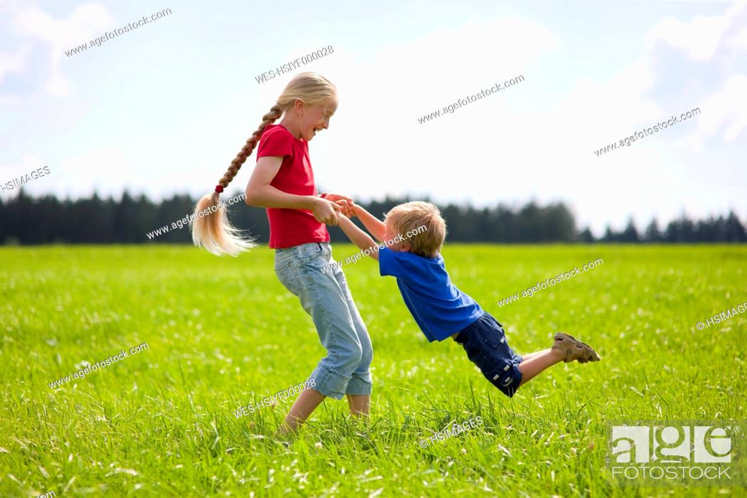 Stock Photo: Germany, Bavaria, Boy and girl playing in meadow.