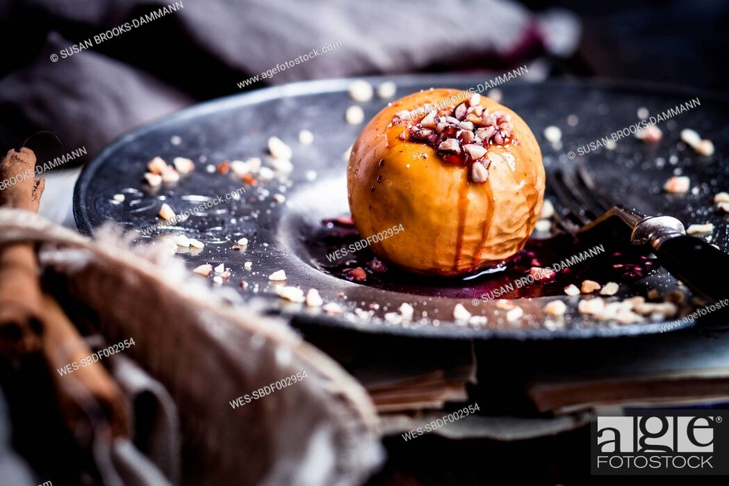 Stock Photo: Baked apple with nut- and red jam filling on tin plate.