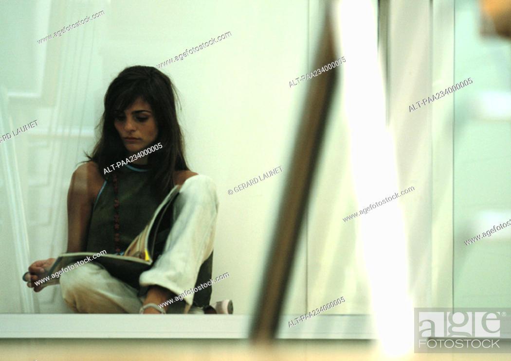 Stock Photo: Woman sitting on ground, legs crossed, reading.