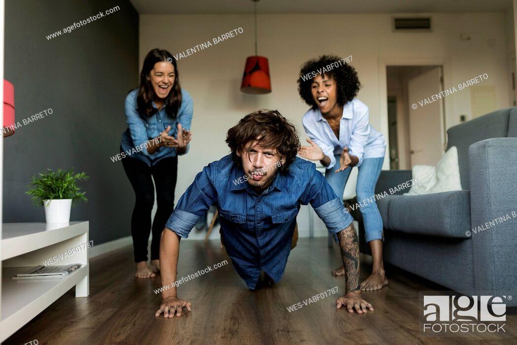 Imagen: Two women encouraging man doing pushups at home.