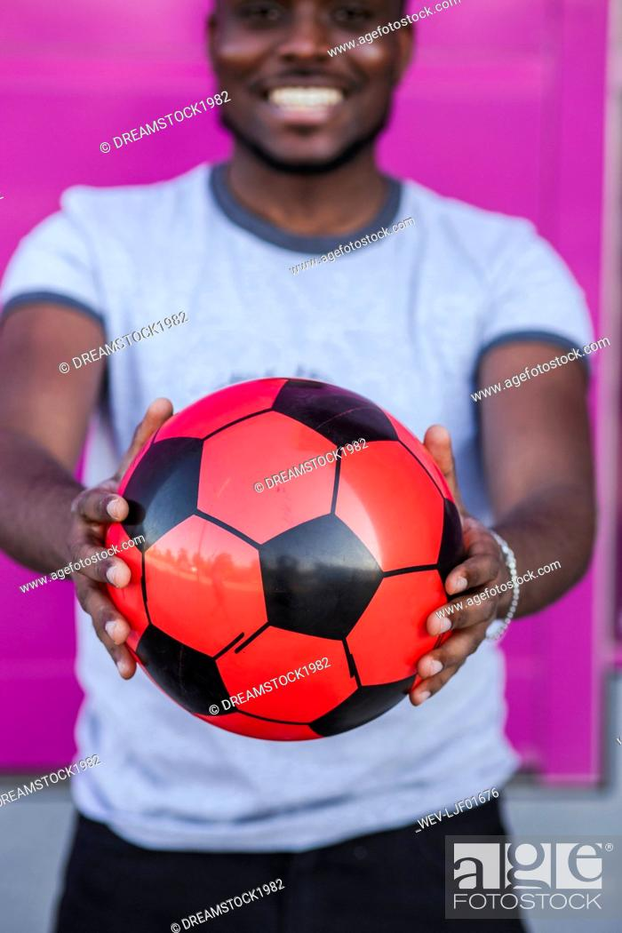 Stock Photo: Close-up of young man holding soccer ball while standing against pink color.