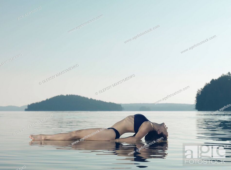 Stock Photo: Young woman practicing yoga on a platform in water on the lake during misty sunrise in the morning. Yoga Fish posture, Matsyasana.