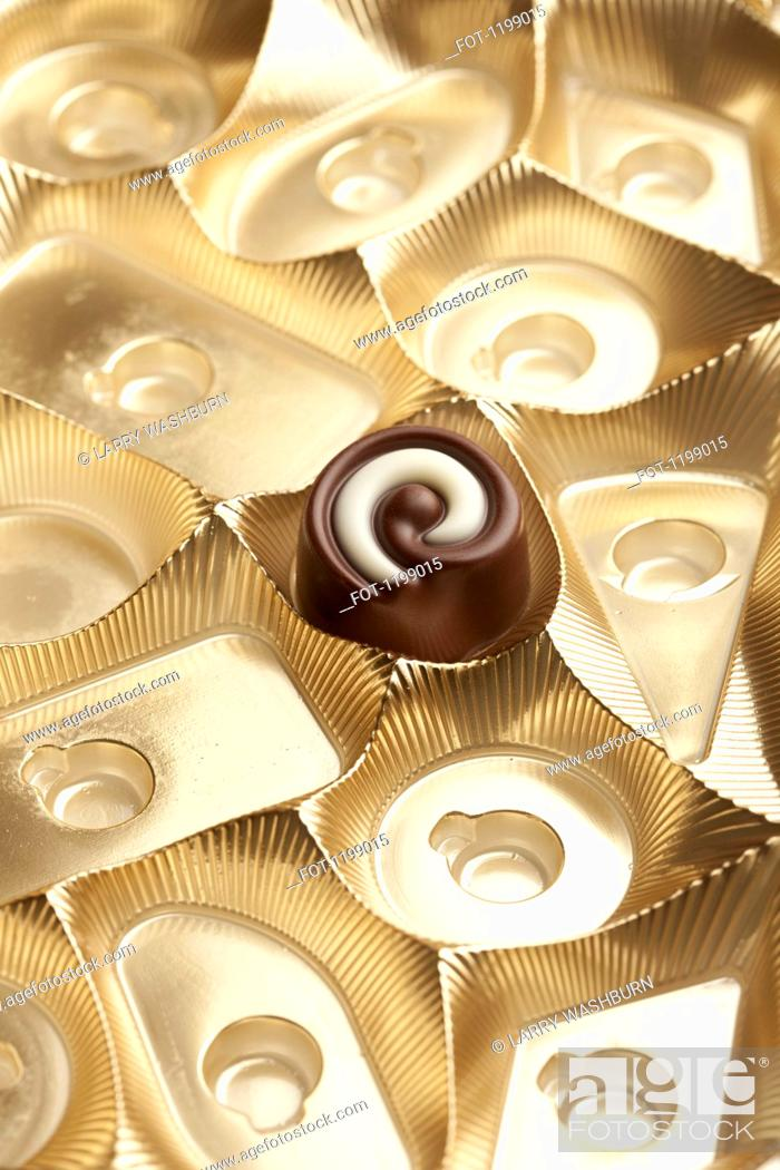 Stock Photo: A single chocolate in a box.