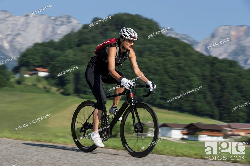 Stock Photo: Germany, Marktschellenberg, sportive woman riding bicycle.