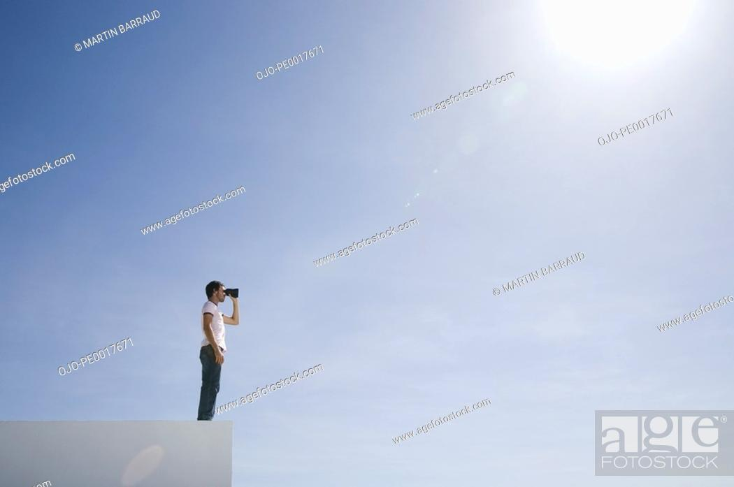 Stock Photo: Man on pedestal with binoculars and blue sky outdoors.