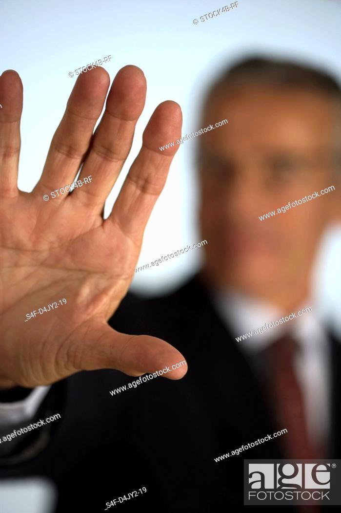 Stock Photo: Senior businessman holding hand at camera.