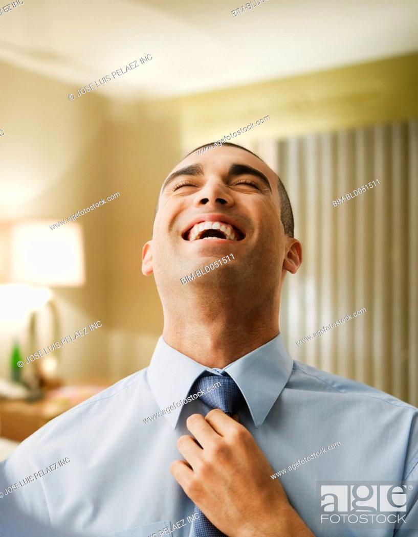 Stock Photo: Hispanic businessman adjusting necktie.