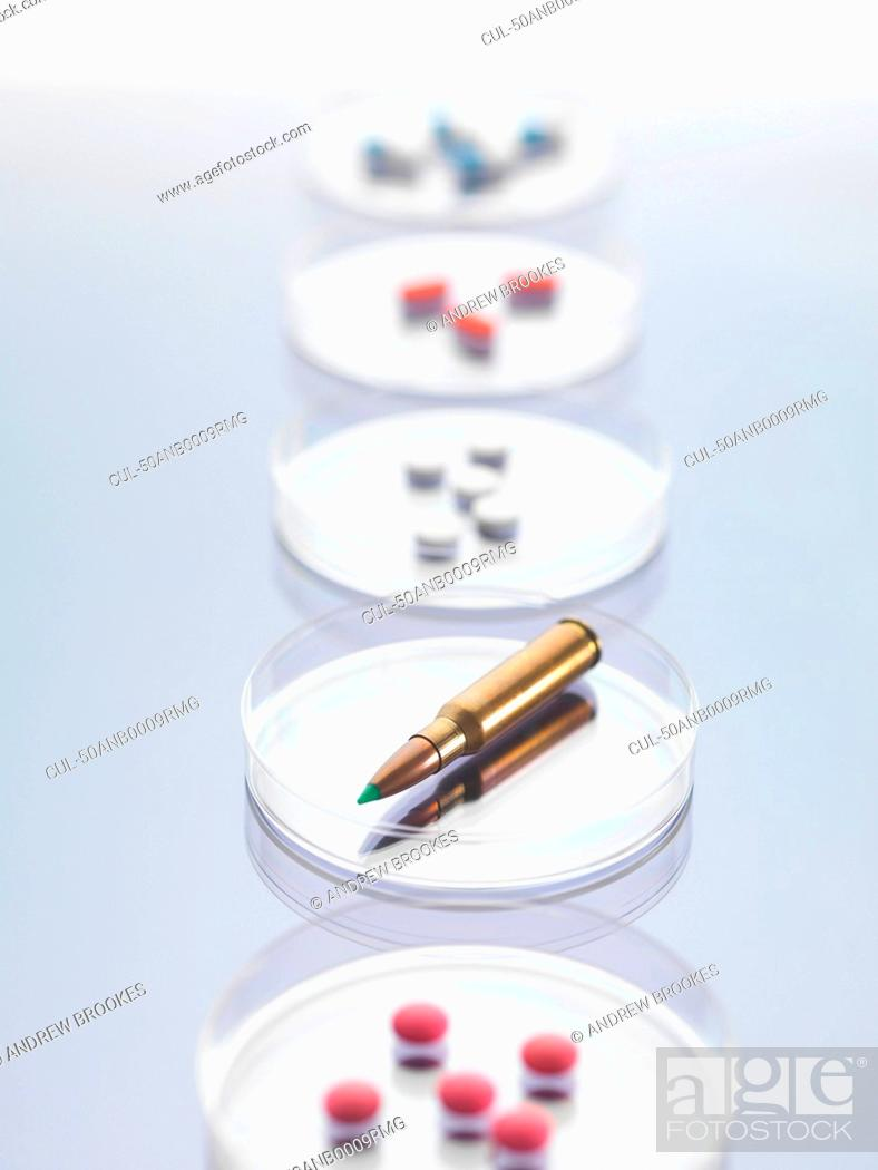 Imagen: Bullet and pills in petri dishes in lab.