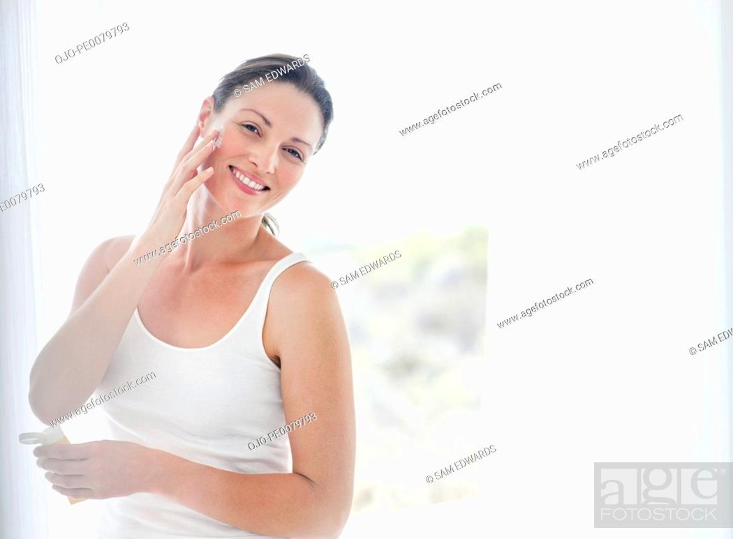 Stock Photo: Portrait of smiling woman applying moisturizer to face.