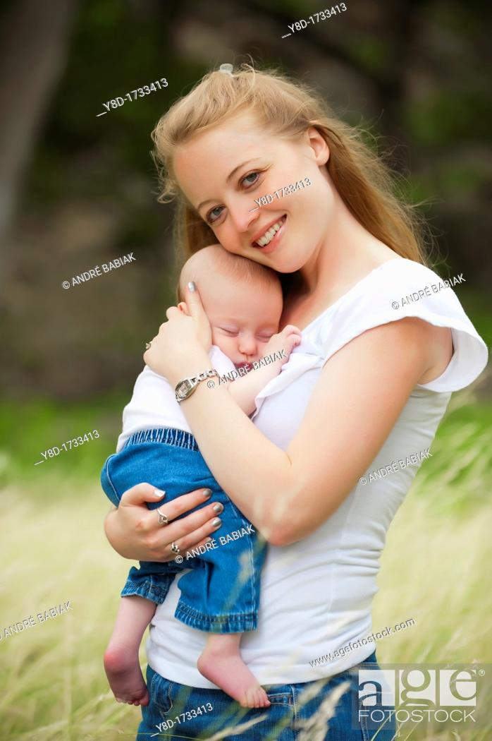 Stock Photo: A young happy mother holding her four months old baby boy in a natural environment.
