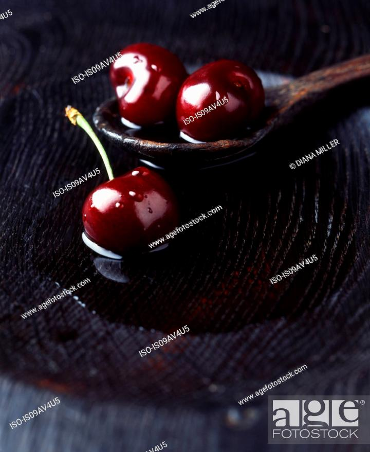 Stock Photo: Fresh black cherries on wooden spoon in bowl of water.