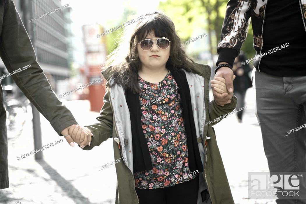 Imagen: daughter holding hands of parents walking in city.