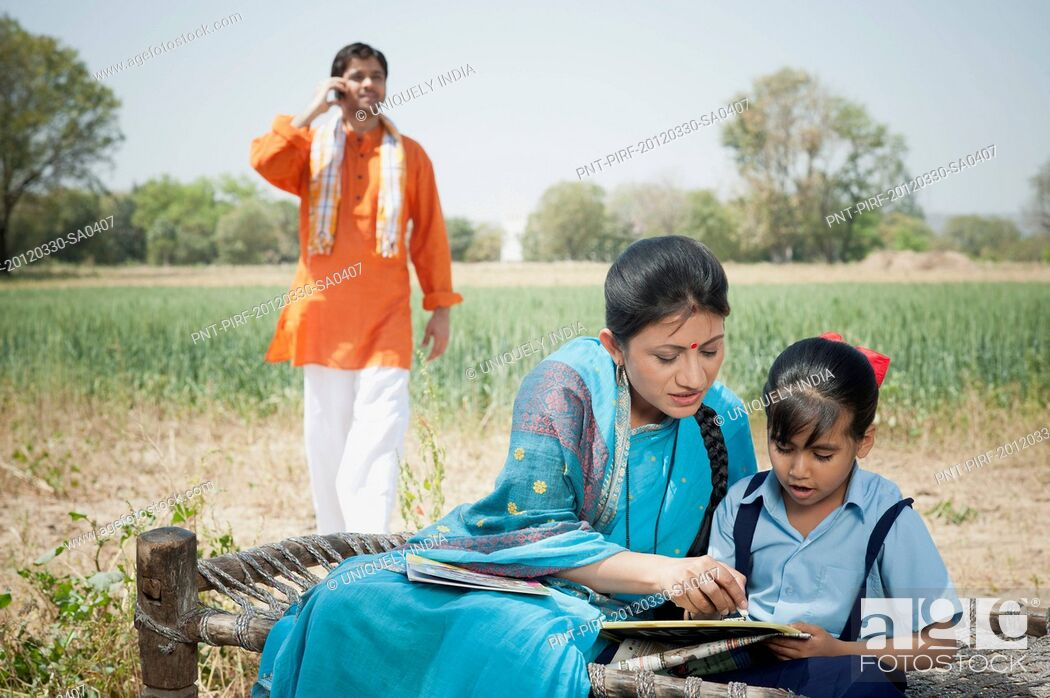 Stock Photo: Woman teaching her daughter with her husband talking on a mobile phone, Sohna, Haryana, India.