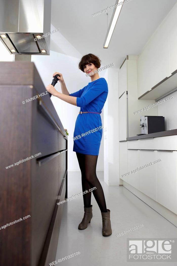 Stock Photo: Germany, Cologne, Young woman with pepper mill in kitchen, smiling, portrait.