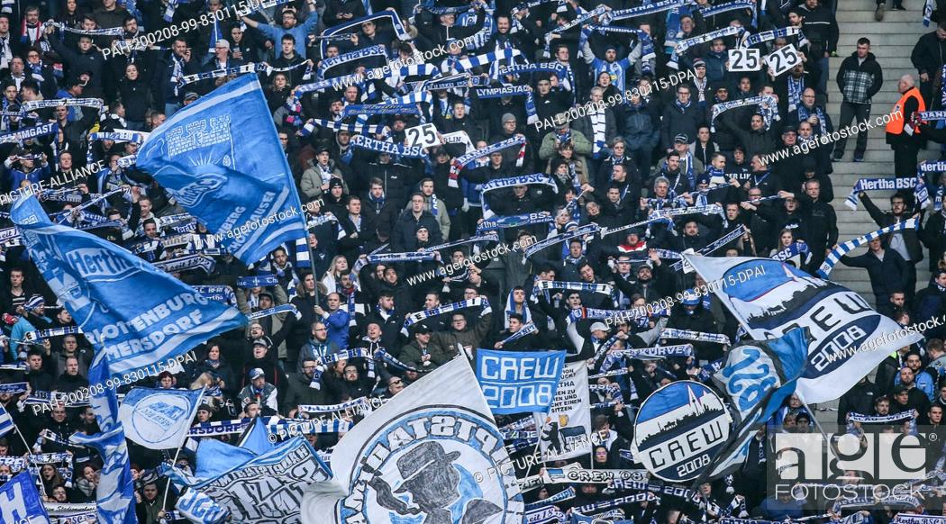 Stock Photo: 08 February 2020, Berlin: Football: Bundesliga, Hertha BSC - FSV Mainz 05, 21st matchday, Olympic Stadium. Fans of Hertha BSC are waving flags in the east bend.