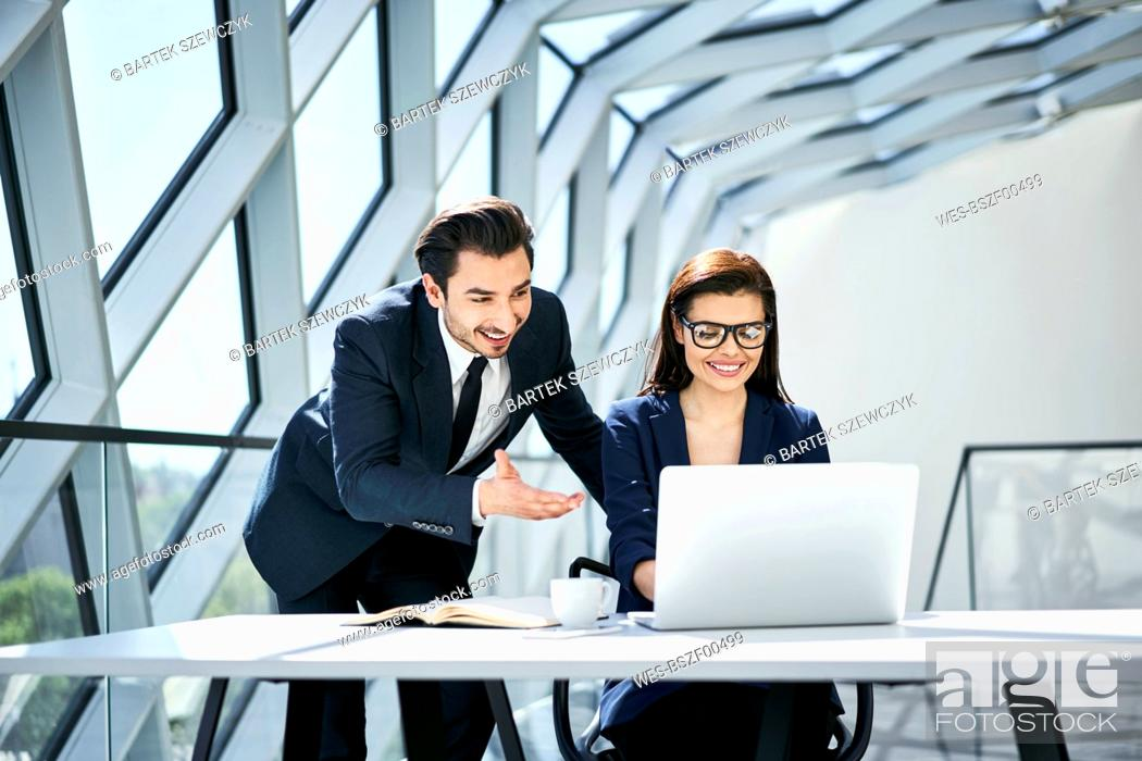 Stock Photo: Smiling businesswoman and businessman using laptop at desk in modern office.