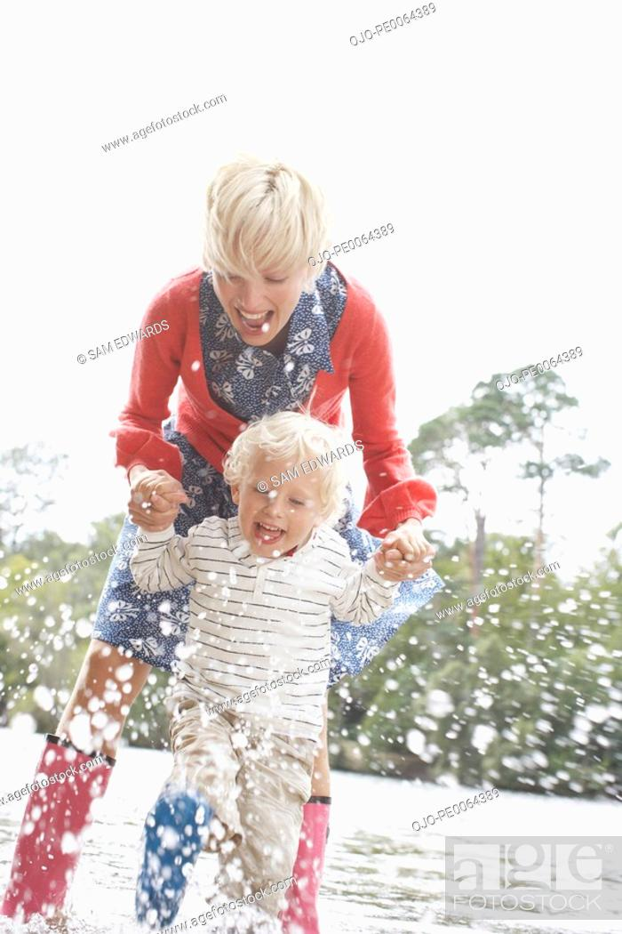 Stock Photo: Mother playing in water with son.