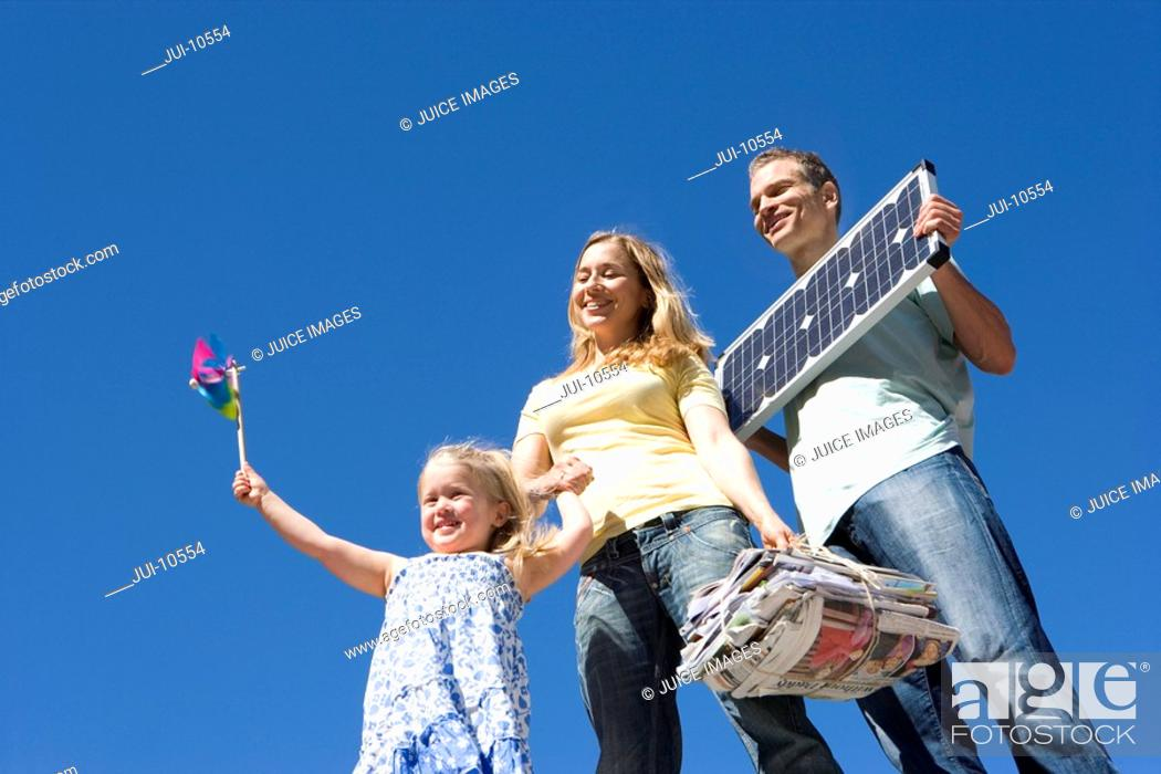 Stock Photo: 30's couple holding solar panel and newspapers for recycling with 5 year old daughter holding coloured windmill outdoors against blue sky,.