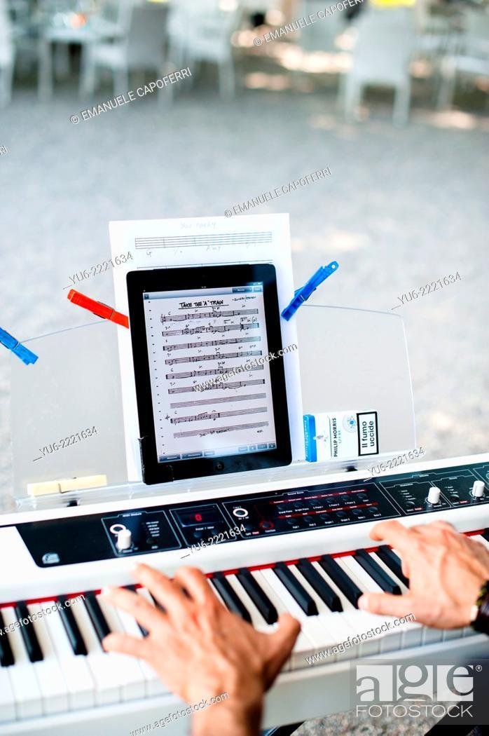 Stock Photo: Pianist plays electronic keyboard, ipad as sheet music.