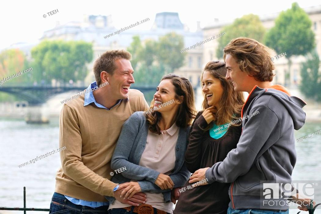 Stock Photo: Group of four young people standing by River Seine, Paris, France.