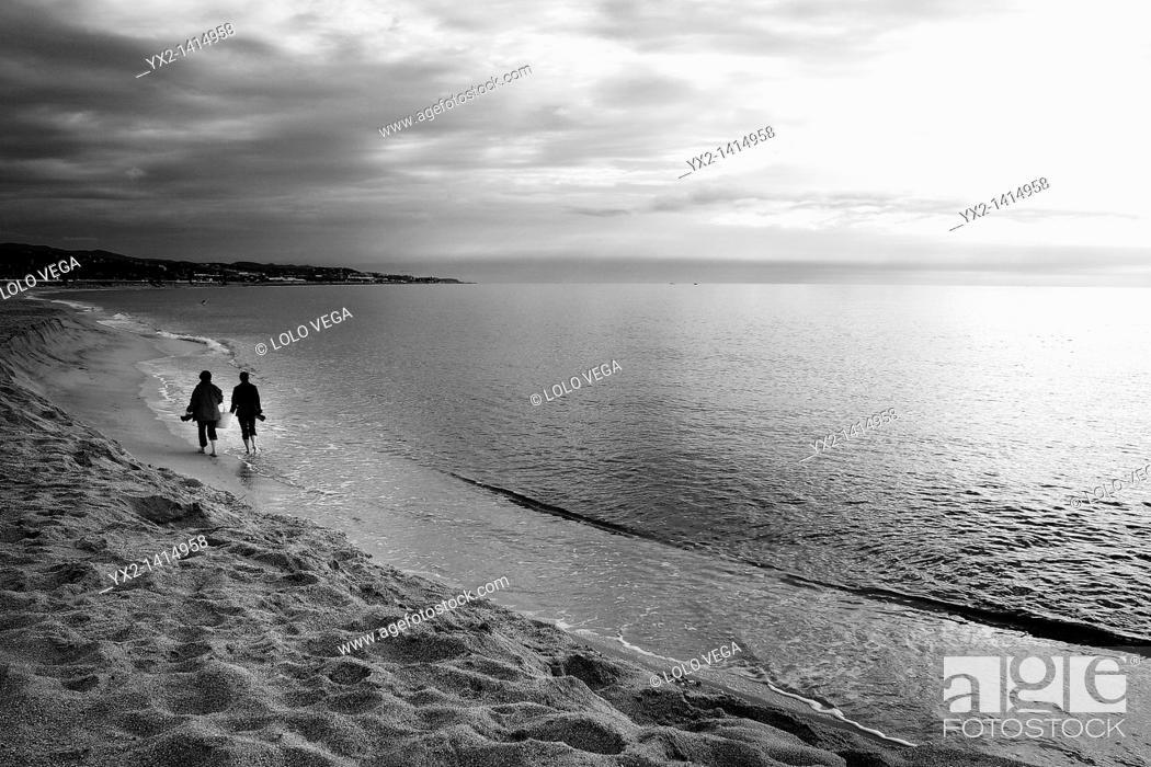 Stock Photo: Couple walking on beach, Mataro, Catalonia, Spain.