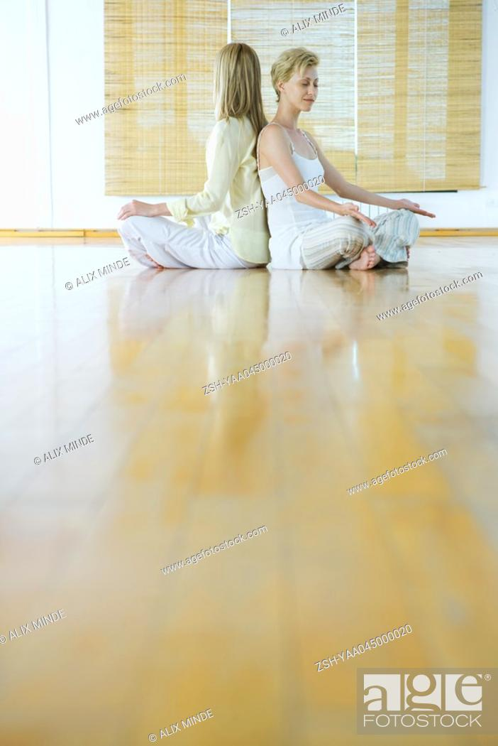 Stock Photo: Group meditation, women sitting on floor back to back.