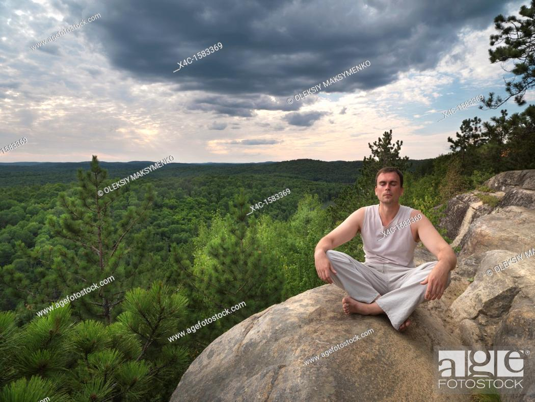 Stock Photo: Young man meditating in the nature  Algonquin, Ontario, Canada.