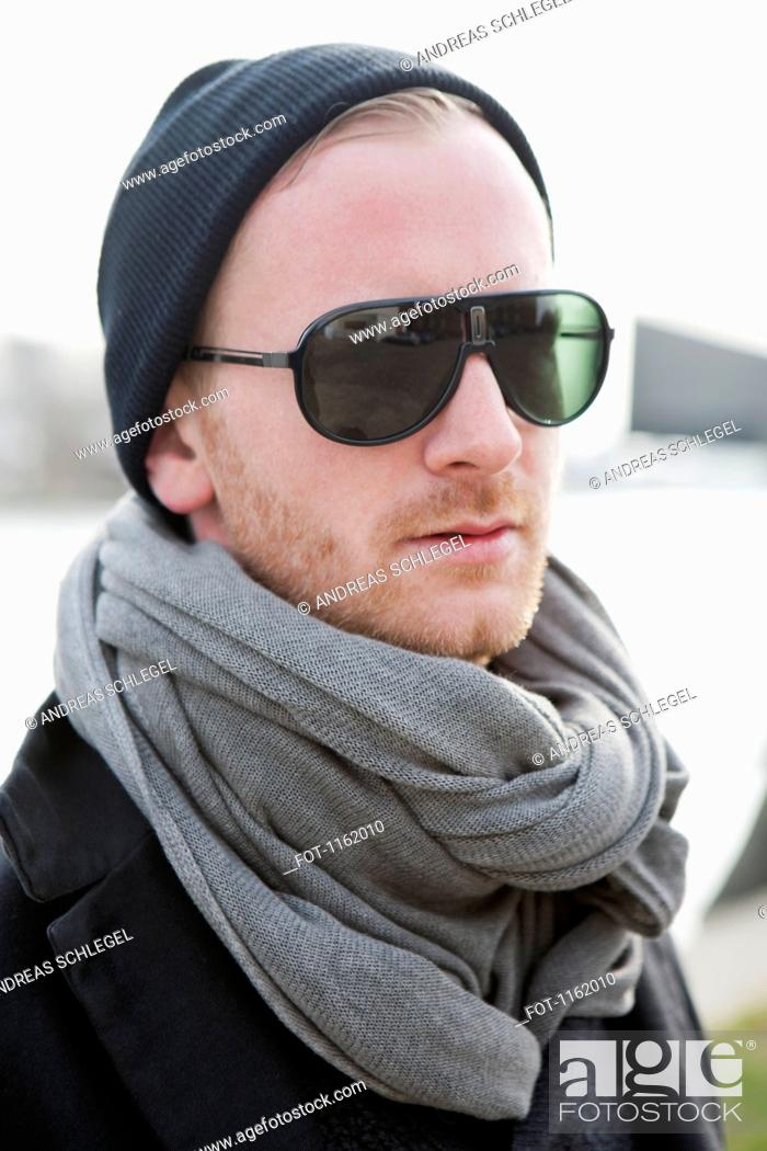Stock Photo: Hipster in grey scarf and sunglasses.