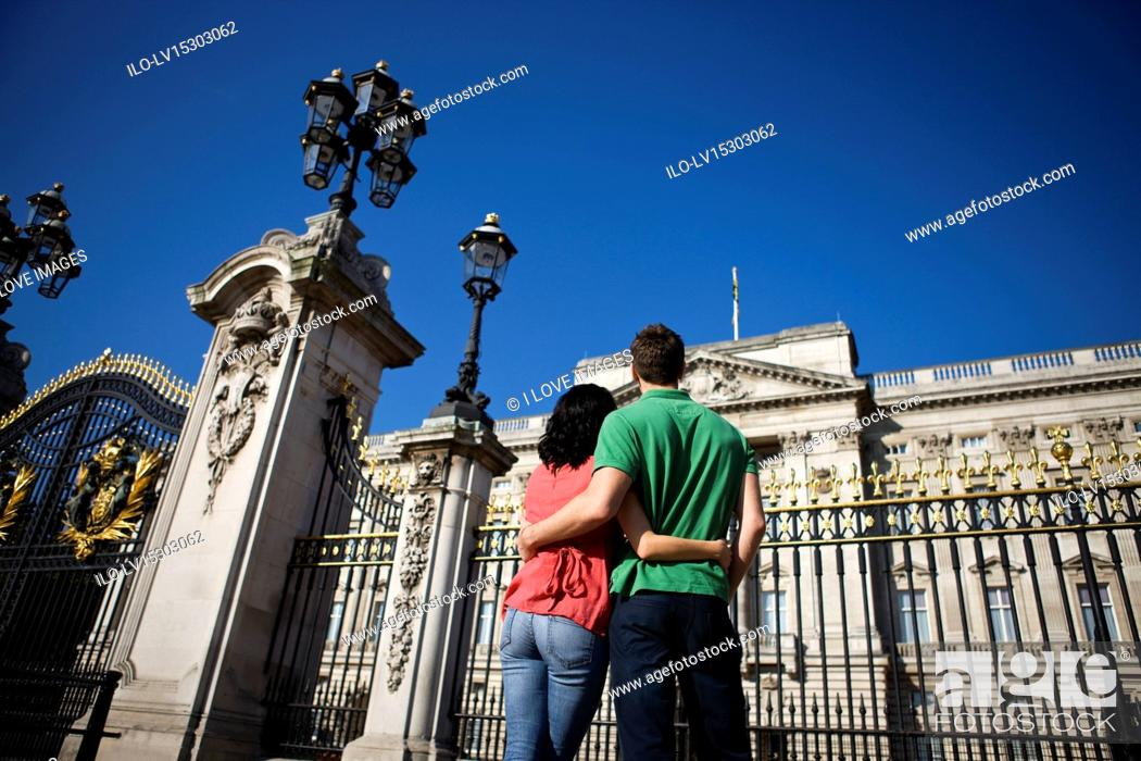 Stock Photo: A young couple standing in front of Buckingham Palace, rear view.