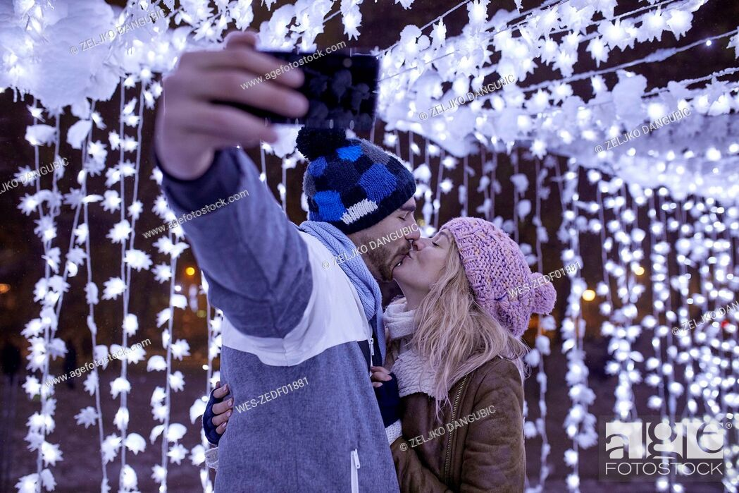 Stock Photo: Young couple in winter decoration kissing and taking a selfie.