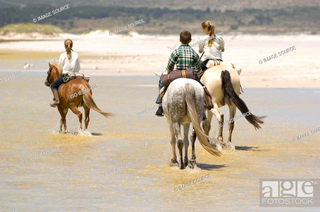 Stock Photo: A boy and girls riding horses.